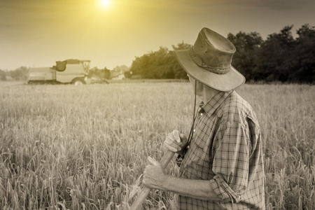 Proud old peasant standing on field with combine in background Stock Photo
