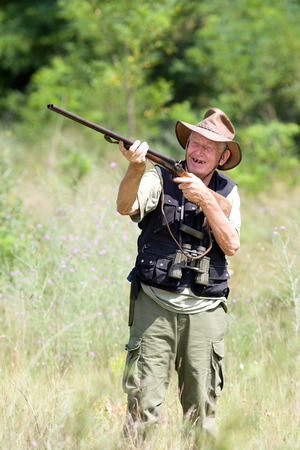 aims: Senior hunter aims his rifle in forest