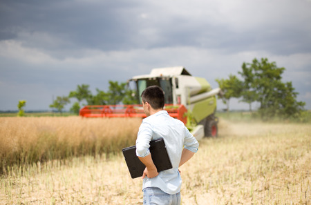 Young businessman with laptop standing in front of combine during harvest