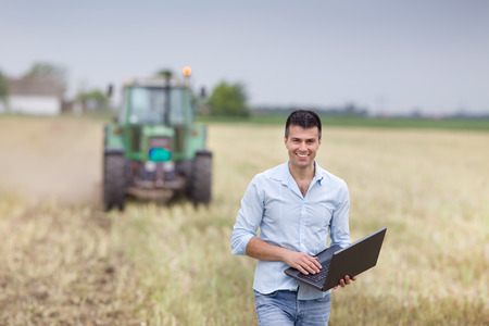 Young attractive businessman with laptop standing in front of tractor with trailers on harvested field