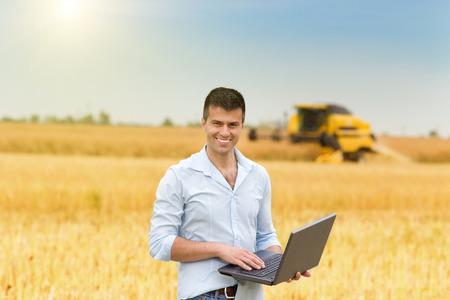 agricultor: Sonriente joven hombre de negocios con ordenador portátil de pie en el campo durante la cosecha Foto de archivo