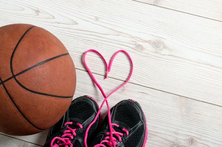 love symbol: Close up of sneakers with lace heart and basketball Stock Photo