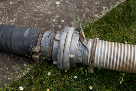 Sewage pipes for extracting septic water from cesspit in courtyard Stock Photo