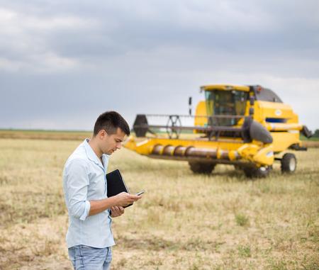 Jonge zakenman met laptop en mobiele telefoon op het veld, maaidorser op de achtergrond