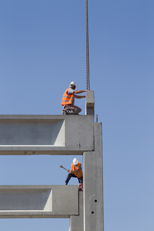 elevator operator: Construction workers standing on concrete beam on height and placing truss lifted by crane Stock Photo