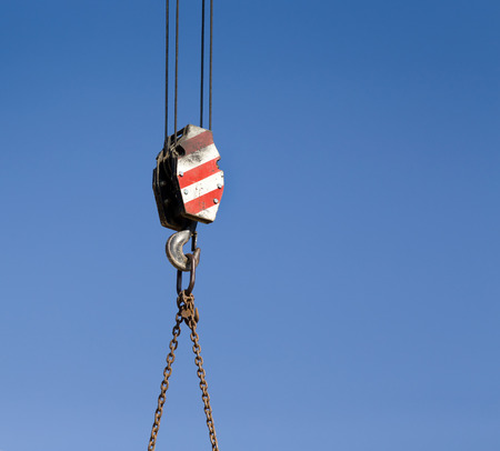 crane parts: Crane hook with red and white stripes hanging, blue sky in background Stock Photo