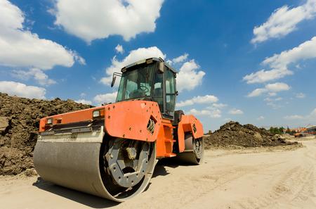 Roestige roll compactor werken op zand gebied op bouwplaats