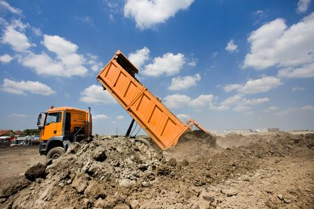 tipping: Orange truck tipping dirt on the construction site, blue sky with white clouds in background Stock Photo