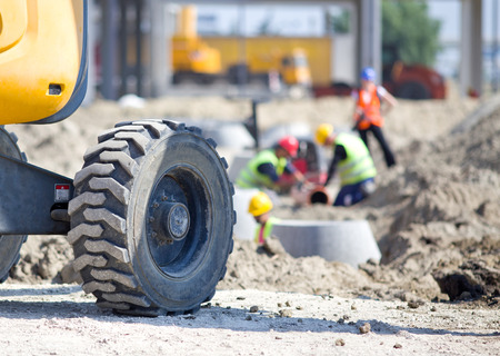 Close up of construction vehicle wheel at construction site and workers  in background
