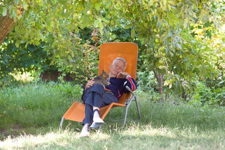 taking nap: Senior man taking nap at sunbed in shade in garden with cat in his lap