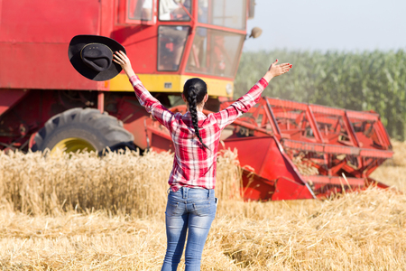 raised arms: Young woman in plaid shirt standing on wheat field with raised arms and hat in hand in front of combine harvester Stock Photo