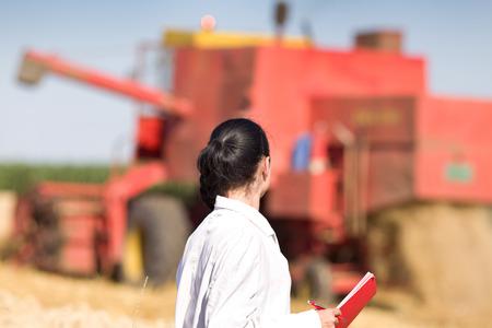 bata blanca: Agr�nomo joven mujer en bata blanca de pie en el campo de trigo dorado durante la cosecha, se combinan en el fondo