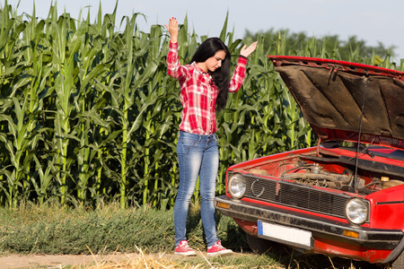 damaged: Young attractive girl standing beside broken car at rural road