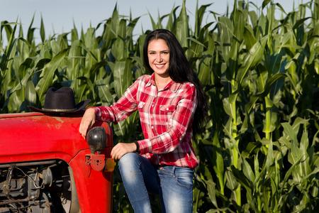 옥수수 밭에 트랙터에 앉아 격자 무늬 셔츠에 검은 긴 머리를 가진 젊은 여자의 초상화