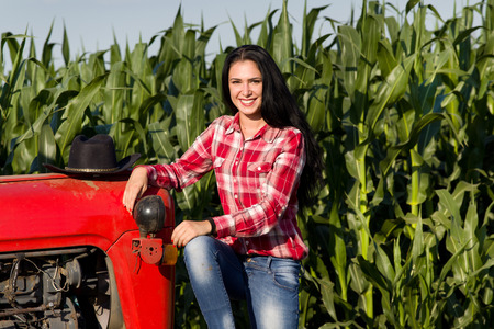Portrait of smiling young woman with black long hair in plaid shirt sitting on tractor in corn field