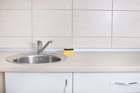 backsplash: Close up of kitchen countertop with sink and sponge for dish cleaning