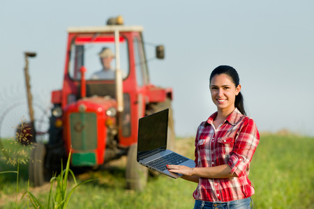 Beautiful young woman with laptop standing in the field with tractor in background Stock Photo