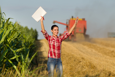 crop harvest: Cheerful beautiful girl in plaid shirt standing in wheat field with raised arms, combine harvester in background
