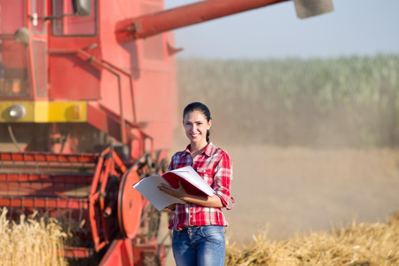 Beautiful girl agronomist with note book standing in golden wheat field and looking at camera, combine harvesting in background