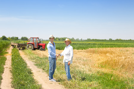Farmer and businessman shaking hands on wheat field Archivio Fotografico