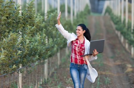 agronomist: Young woman agronomist with laptop waving hand and walking beside apple trees in modern orchard with anti hail net