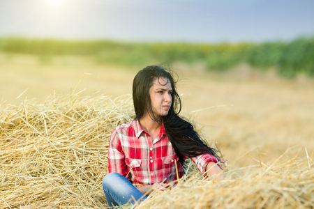 plaid shirt: Portrait of young beautiful girl in plaid shirt sitting on straw pile on field while powerful wind blowing her long black hair
