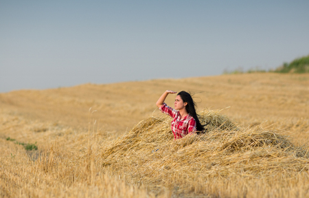 far away: Young girl sitting on straw pile after harvest and looking far away at sun