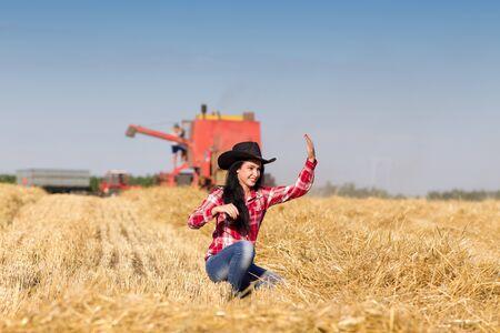 en cuclillas: Hermosa joven con sombrero de vaquero en cuclillas en el campo whet cosechado, cosechadoras y tractores con remolque de trabajo en segundo plano