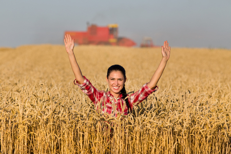 harvest field: Happy young woman standing in golden wheat field during harvest Stock Photo