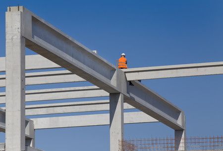 elevator operator: Construction worker sitting on concrete beam on height and waiting crane to lift truss for installation