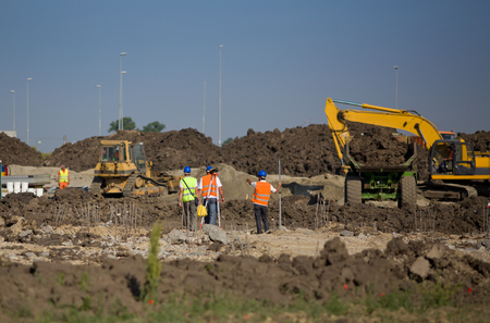 Construction workers measuring ground level at road construction site Stock Photo