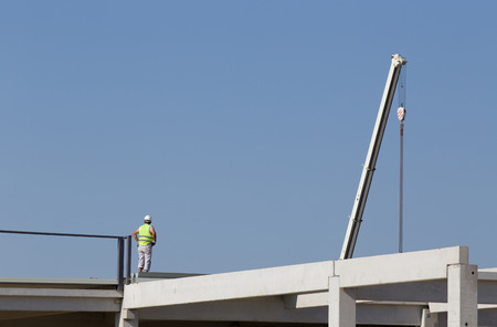 rigger: Construction worker standing on concrete beam on height and waiting crane to lift truss for installation