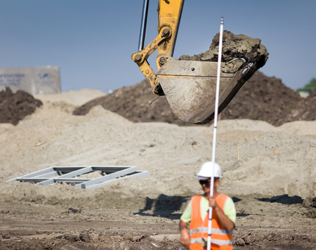 leveling instrument: Construction worker standing with leveling rod at building site, excavator bucket in background