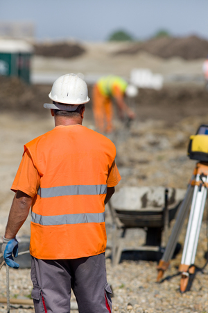 tachymeter: Construction workers standing on building site and looking at worker with jackhammer