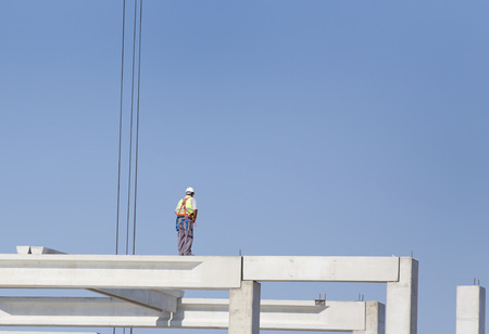 elevator operator: Construction worker standing on concrete beam on height and waiting crane to lift truss for installation
