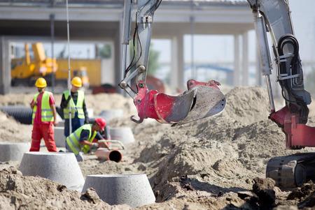 Pequeño excavadora y trabajadores en el sitio de construcción