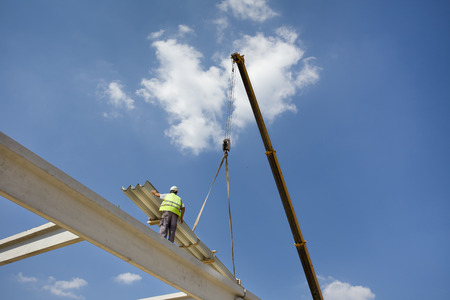concrete construction: Construction worker standing on concrete beam on height and placing roof materials lifted by crane