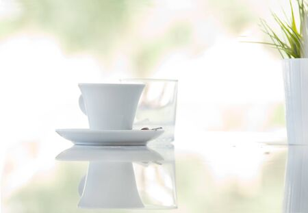 morning breakfast: Cup of coffee with glass of water on reflective surface of cafe table with dreamy background