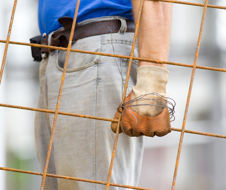 steeplejack: Close up of workers hand with safety gloves carrying rusty reinforcement mesh