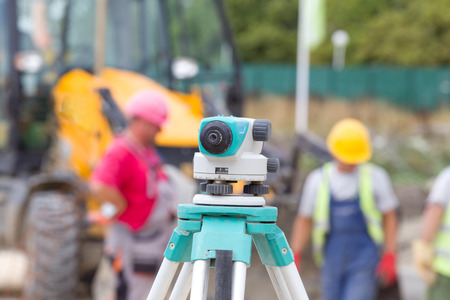 leveling instrument: Surveying measuring equipment level theodolite on tripod at construction site with workers in background