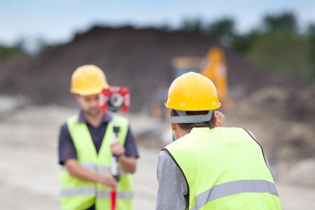 ingeniero: Ingenieros Surveyor trabaja con teodolito en el sitio de construcción de carreteras