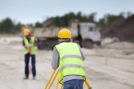 leveling: Surveyor engineers working with theodolite on road construction site