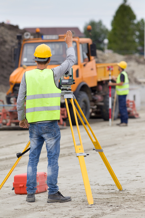 tachymeter: Surveyor engineers working with theodolite on road construction site