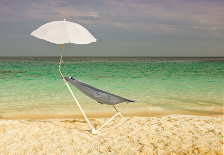 positioned: Blue sunbed with small parasol positioned on the sandy beach next to azure blue water Stock Photo