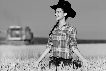 black cowgirl: Cowgirl with plaid shirt and hat walking in ripe wheat field during harvest, black and white image