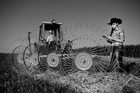 black cowgirl: Young girl farmer standing beside haying rake attached to tractor, black and white image Stock Photo