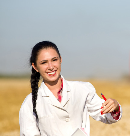 agronomist: Portrait of young smiling woman agronomist in golden wheat field