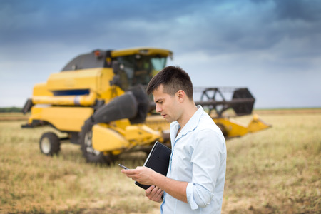 cell phone: Young businessman standing with laptop and cell phone on field, combine harvester in background