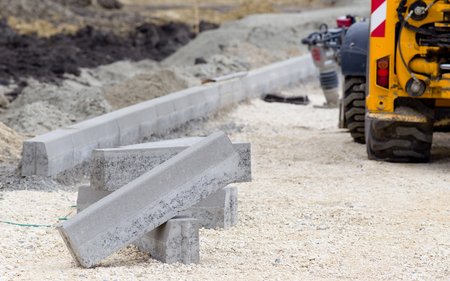 kerb: Kerb stones on gravel ground for placing road edge at construction site