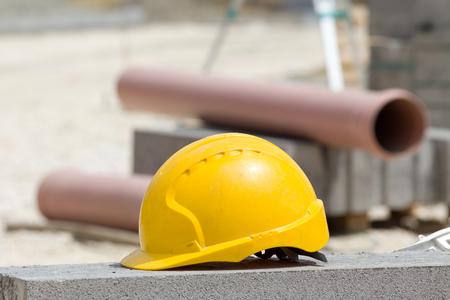 materiales de construccion: casco amarillo de pie en la carretera de hormig�n en el sitio de construcci�n. Las tuber�as de pl�stico y bloques de carretera en el fondo